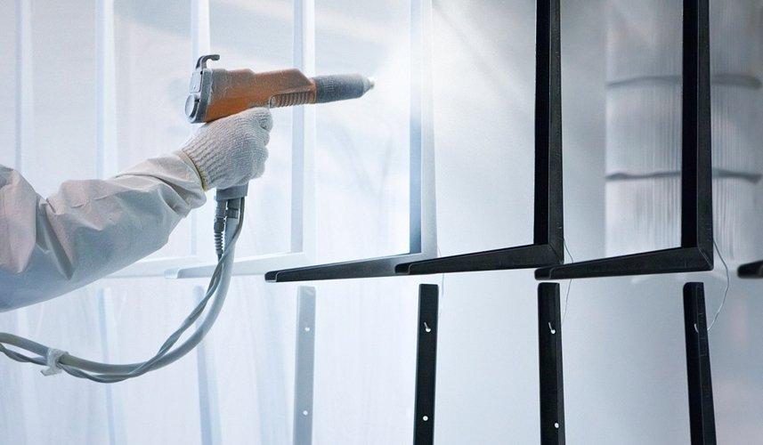 person spraying powder coating